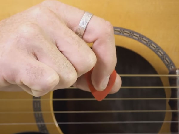 Index finger pointing down on pick in how to hold a guitar pick lesson
